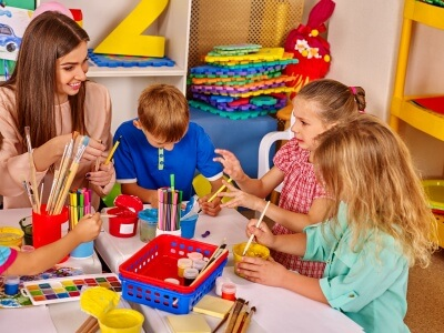 children and teacher doing painting